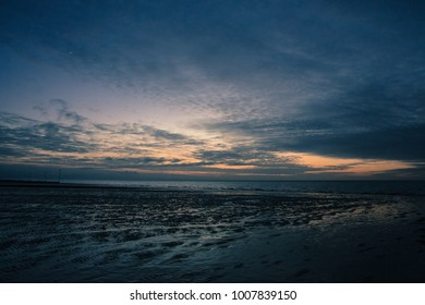 Big sky over receding tide and wet beach