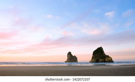 A big sky over Wharariki Beach in New Zealand lights up with pastel colors at sunset