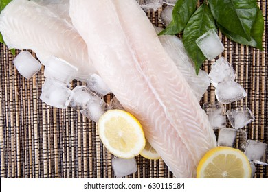 Big slice of fish raw food with ice cube, lemon and green leaf