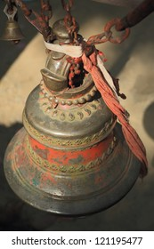 Big and small bronze bells with red and white fabrics, hanging from chains at the entrance to the Dakshin Kali hinduist temple, Pharping, Kathmandu, Nepal.