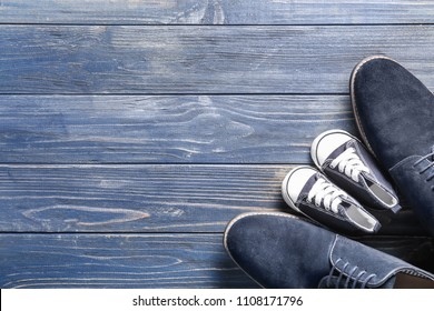Big and small shoes on wooden background. Father's day celebration