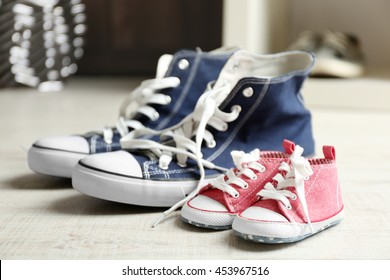 Big and small shoes on wooden floor