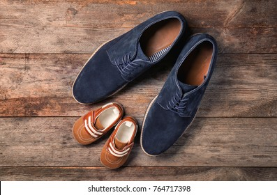 Big and small shoes on wooden background. Father's day composition