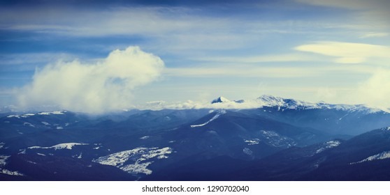 big snow mountain top above clouds, winter mountain range panorama