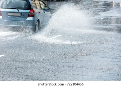 big splashes of rainwater from car wheels. city traffic during heavy rain.