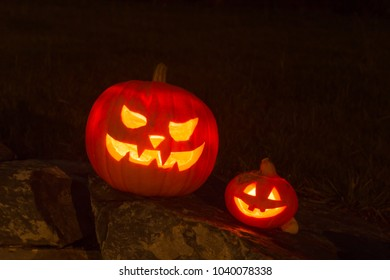 Big Spooky and small funny Halloween Pumpkin in the dark night on a stone wall