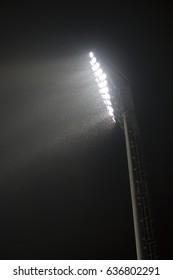 big spot light in football stadium night and bug