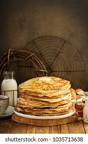 Big stack of homemade crepes or thin crepes with butter in rustic style