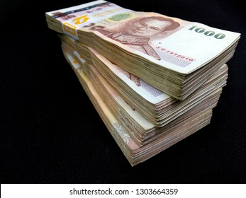 A big stack of Thai baht cash money bank notes on black background.