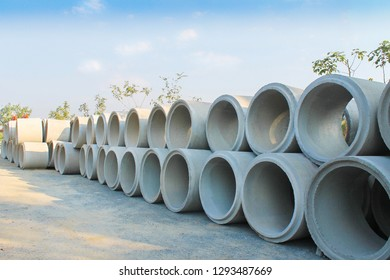 Big stacks of concrete sewage pipes on the ground prepare for underground instalation and blue sky background