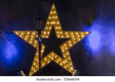 A big stage star with lamps in the studio. Retro microphone on a star background.