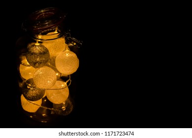 Big standing glass jar filled with yellow lightning lampions with the black background