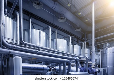 Big steel tanks reservoirs for alcohol beer production at modern brewery, blue toned as abstract industrial background with pipeline