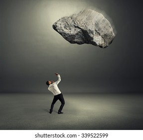 big stone falling down on scared businessman over grey background
