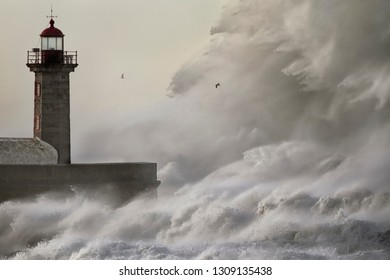 Big stormy sea crashing wave. Douro river mouth old lighthouse and pier, Porto, Portugal.