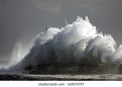 Big stormy wave against pier and lighthouse