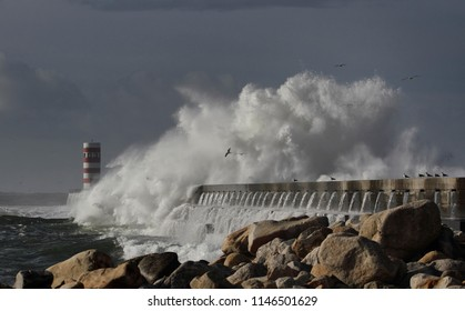 Big stormy wave splash against dark sky before rain. Douro river mouth south pier and beacon, north of Portugal.