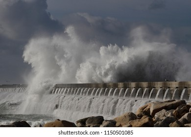Big stormy wave splash against dark sky before rain. Douro river mouth south pier, north of Portugal.