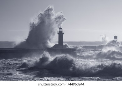 Big stormy wave splash. Douro river mouth old lighthouse and pier, Porto, Portugal. Used infrared filter. Toned blue.