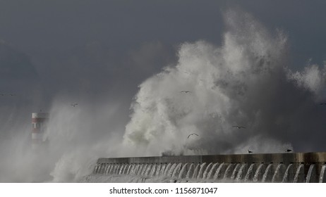 Big stormy wave splash and spray over pier and beacon. North of Portugal.