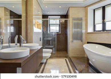 Big and stylish bathroom in brown and beige colors, with ceramic bath under window, big mirror on wall, two sink and bowl. Shower cabin with glasses wall.