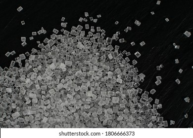 Big sugar crystals texture on black background close up. Macro shot of sucrose crystals, sea salt rock or granulated sodium salt pattern on food slate top view and flat lay