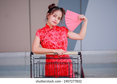 Big summer sale Chinese New Year Festival! Beautiful gorgeous Asian woman in traditional Chinese dress holding Ang Pow and pushing supermarket cart.