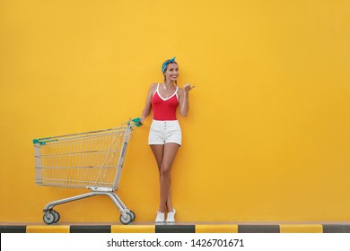 Big summer sale! Young smiling woman posing next to an empty shopping yellow wall.