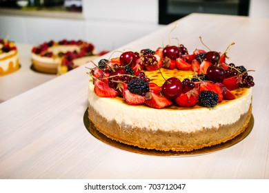 Big sweet cake with many different fruits on the kitchen