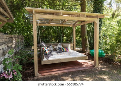 Big swing outdoor bed. Chaise longue in the garden in the pergola. Garden bed with pillows. Big outdoor bed for sunbathing and rest.  Bed in the garden in the pergola.