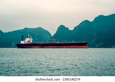 Big tanker anchored in Bay. A large transport ship in the sea against the background of high rocks. Vietnam, Ha long.