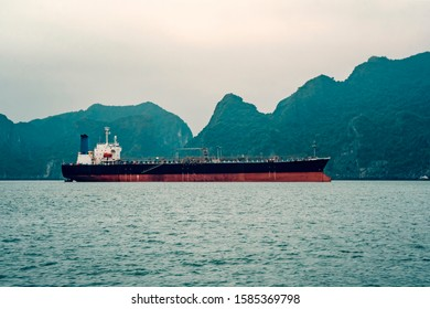 Big tanker anchored in Bay. A large transport ship in the sea against the background of high rocks. Vietnam, Ha long