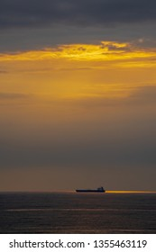 Big tanker vessel on the horizon at sunrise. Tanker vessel waiting on the roads of the port.