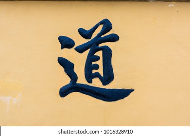 Big tao symbol of the way or path in Chinese as black character on yellow background