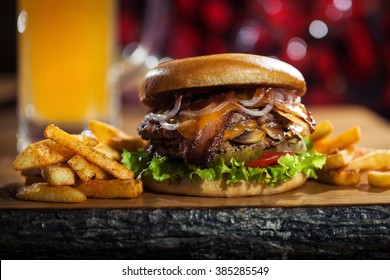 Big tasty burger and fries with beer on background on the wooden table