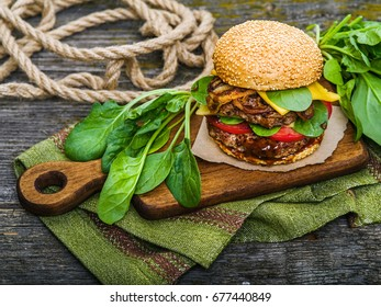 Big tasty hamburger with spices and herbs on wooden board and on table