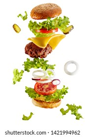 Big tasty home made burger with flying ingredients on white background. Isolated.