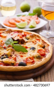 Big tasty pizza with seafood, tomatoes and white wine on wooden table closeup