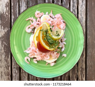 Big tasty and typical Swedish dish with shrimp sandwich served on a green ceramic plate on wooden table.