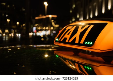 The big taxi sign on the background of night city