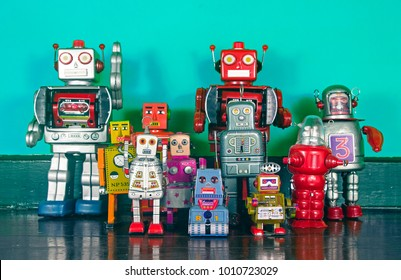 a  big team of retro robots on a wooden floor