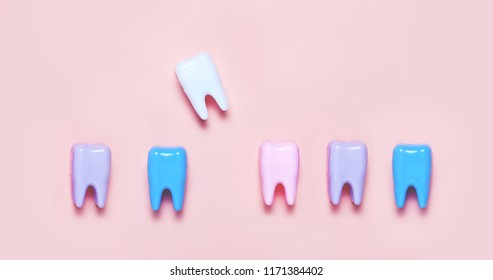 Big teeth on blue and pink background. Teeth care minimalism concept. Loosing teeth concept. Top view,