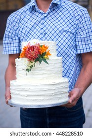 Big three tiered wedding cake decorated with fresh flowers in man's hands, selective focus