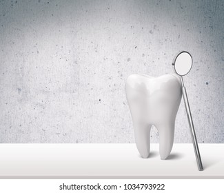 Big tooth and dentist mirror on table