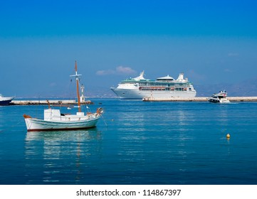 The big tourist liner and fishing boats in a port