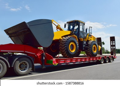 Big tractor machine heavy tool on truck transportation motion speed on road under blue sky