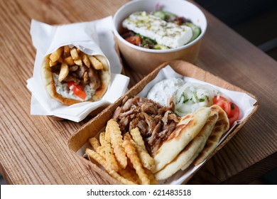 Big traditional Greek cuisine dinner served on table in paper plate.Fast food mediteranean restaurant menu dishes.Enjoy roasted meat souvlaki dish & fried gyros roll.Junk food menu