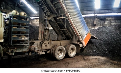 Big truck was dumping a lot of coal in the warehouse