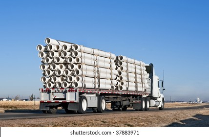 Big truck with flatbed trailer hauling plastic pipe.
