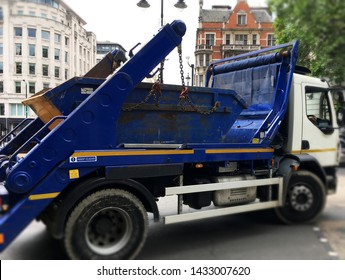 Big truck loaded with blue industrial skip. Selective focus on the metal bin on back of the vehicle with blurry surrounding area of truck, wheels, buildings as space to add text for background use.